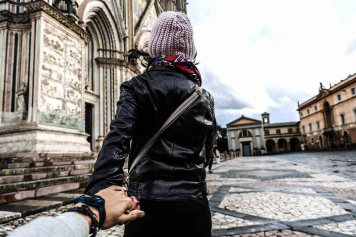 man holding woman hand while walking
