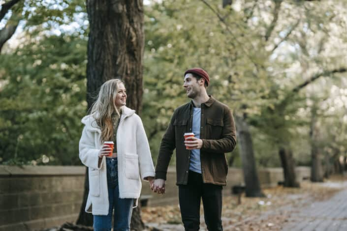 positive young couple holding hands and drinking coffee