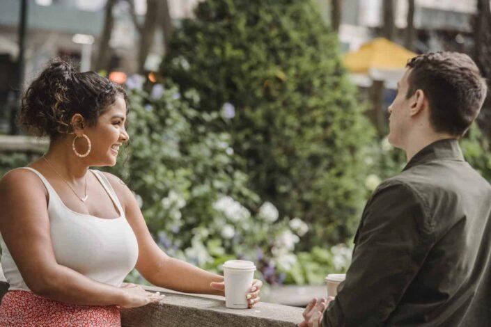 Couple drinking takeaway coffee on terrace