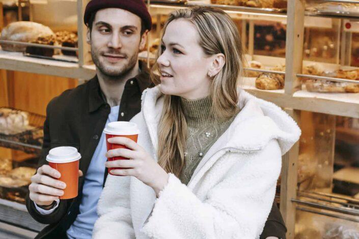 Smiling couple enjoying their coffee in a coffeeshop