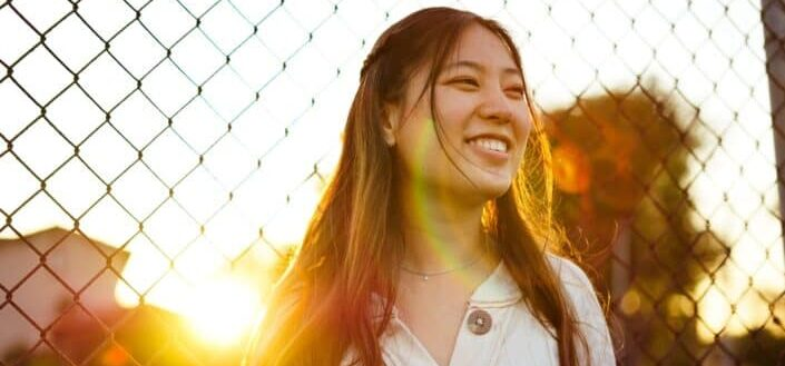 woman smiling on fence during golden hour