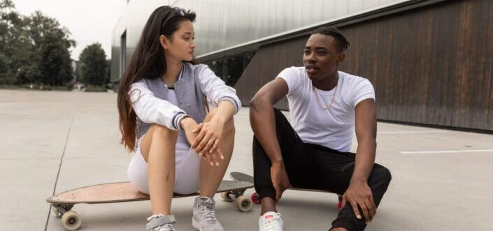 Skater couple talking while sitting on their skateboards.
