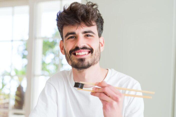 Young man eating sushi using chopsticks