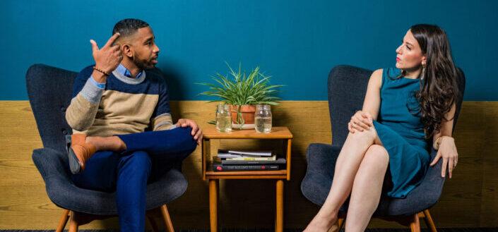 Woman wearing teal dress sitting on chair talking to man