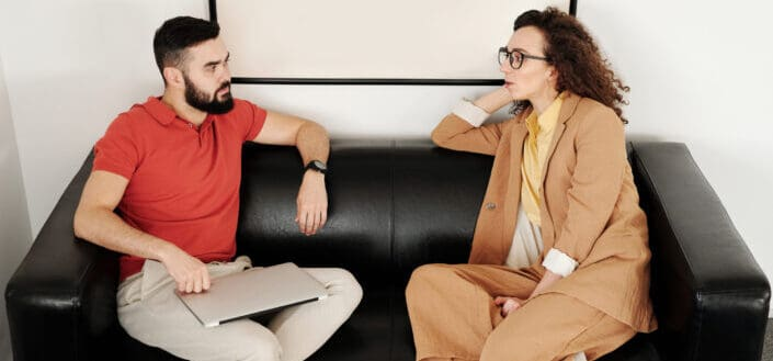 two adults having serious conversation in a couch