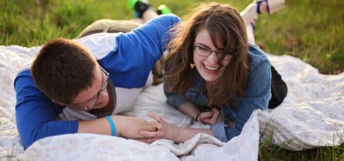 Two person laying on white mat, having fun.
