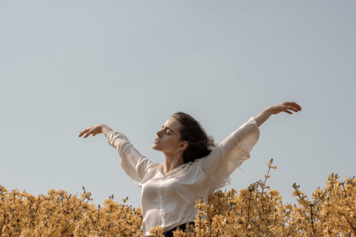 a carefree woman enjoying the breeze under a clear sky