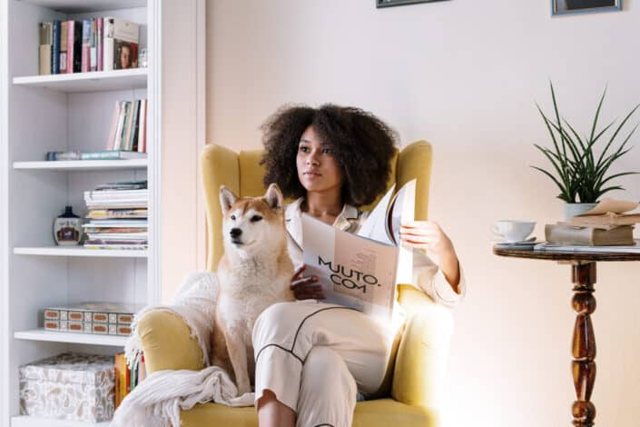 woman in a pajama sitting on a couch with her dog