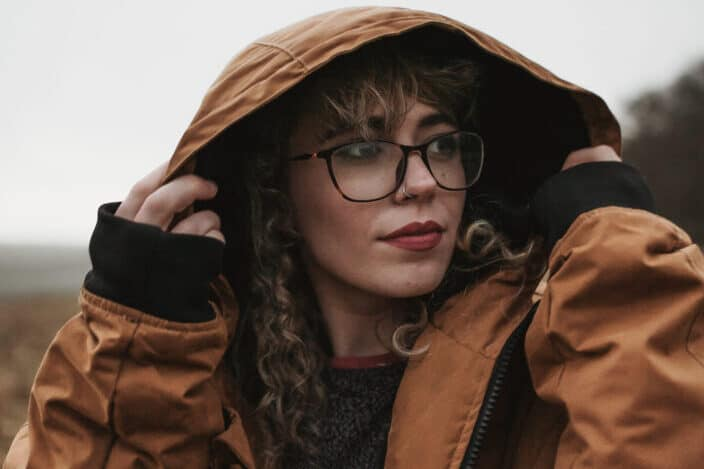 a woman in a brown jacket staring at something beside her