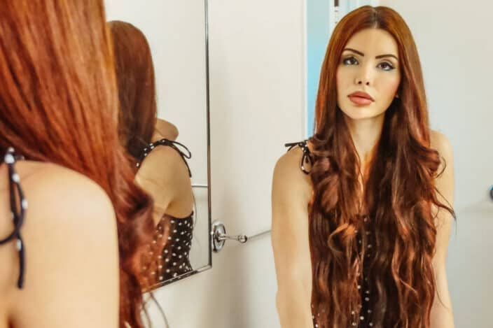 a stunning woman staring at herself in the mirror