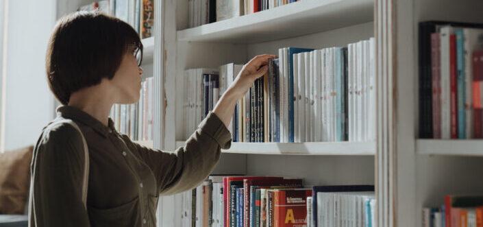 Woman choosing a book from the shelf.