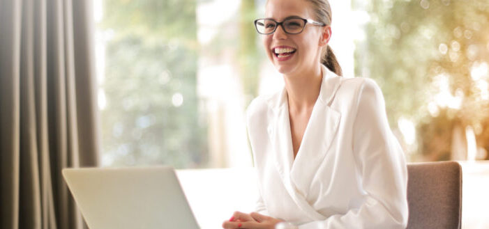 Laughing businesswoman working in office with laptop