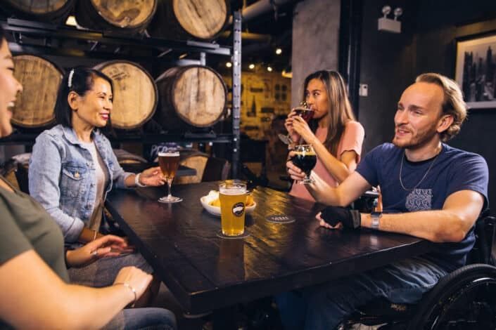 Four friends drinking a variety of beer and wine