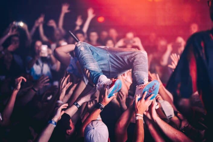 Man being lifted by people at a concert.