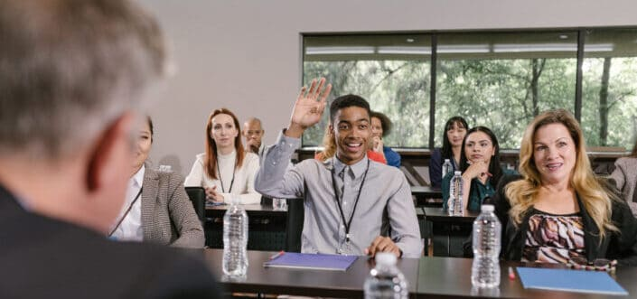 Man in a meeting raising his hand to ask a question.