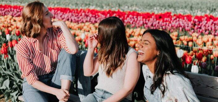 Three friends sitting and laughing on a bench in a flower garden.
