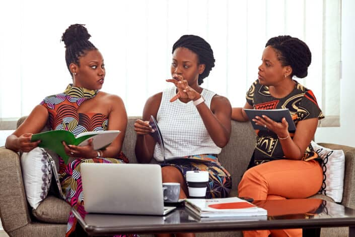 Three women discussing on a couch.