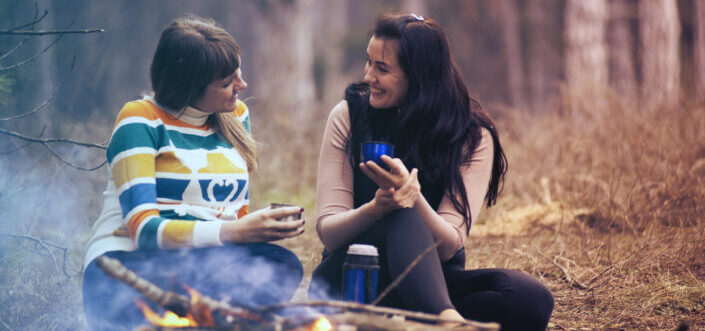 Two female friends having a deep conversation in the forest.