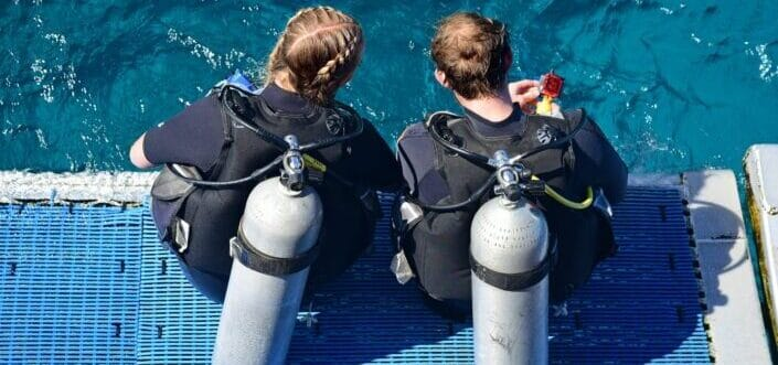 Two female scuba divers ready to dive into the water.