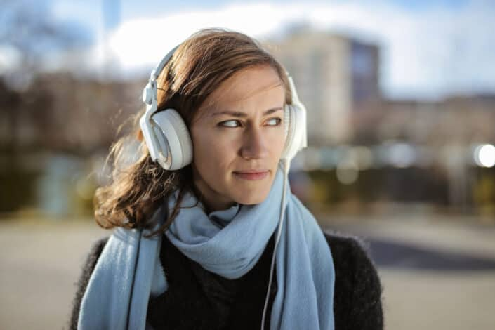Woman walking while listening to music through her headphones.