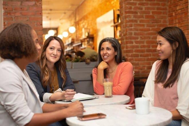 women talking while having snacks - alpha female