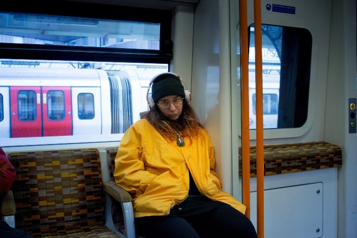 woman riding a train while listening to music