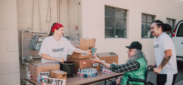 Old man receiving relief goods from volunteers