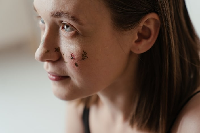 Woman With Floral Art Tattoo on Her Face