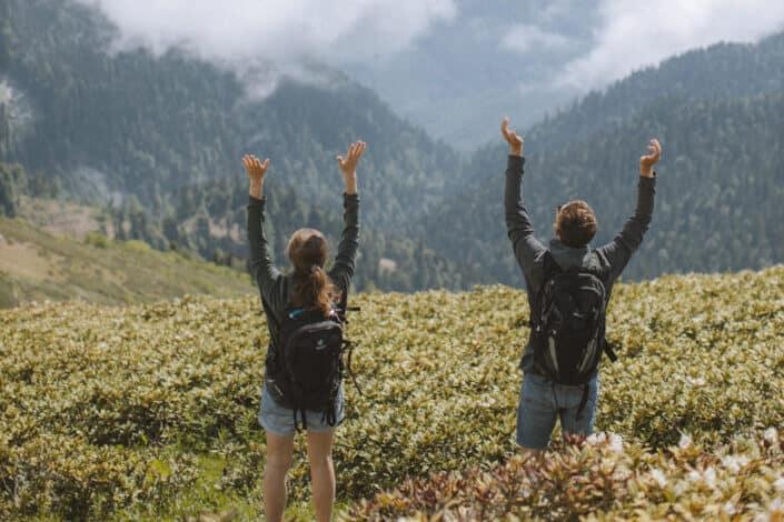 couple celebrating as they climb the mountain's peak.