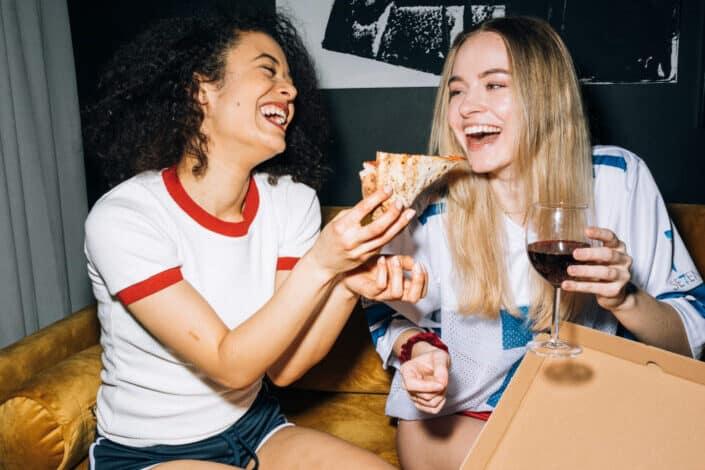 Women Having Fun While Eating Their Pizza