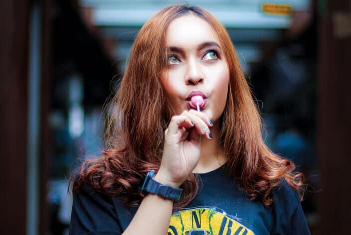Woman having a stick of lollipop.