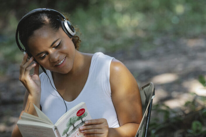 Woman reading a book while listening to music