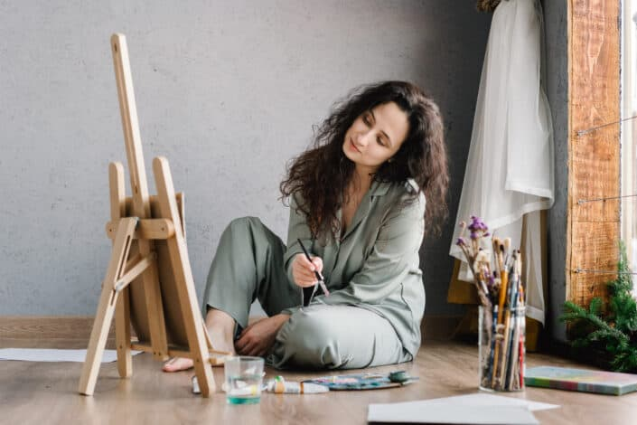 Woman sitting on the floor while painting.