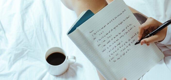 Woman writing while having coffee