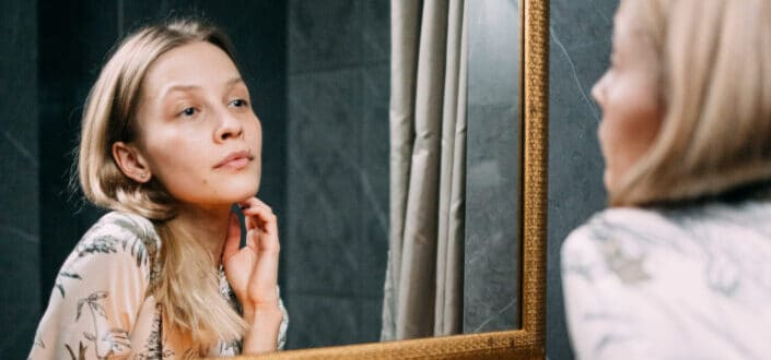 woman feeling pretty while looking at her reflection