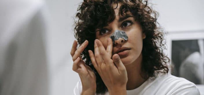 Curly woman applying nose strip in bathroom