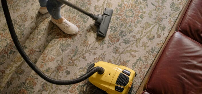 Person Holding Yellow and Black Vacuum Cleaner