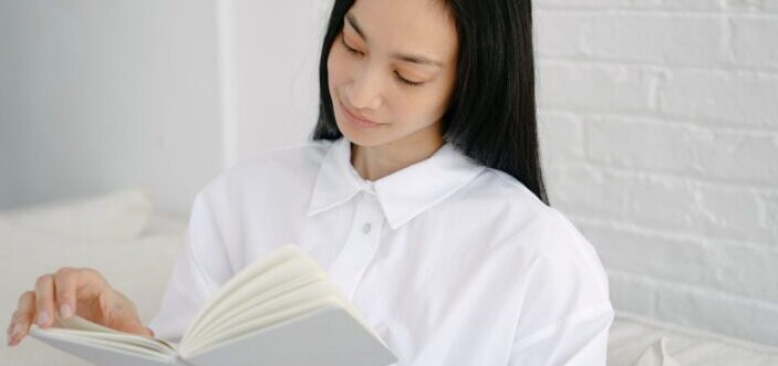 Woman flipping page of book.