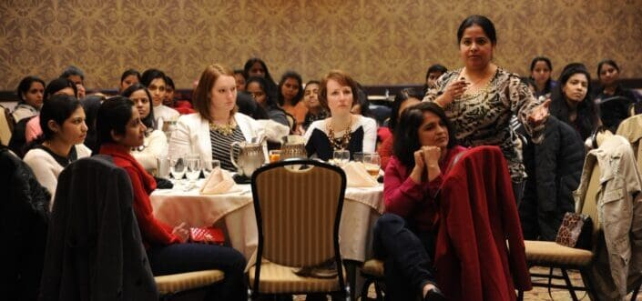 Woman asking a question while in a conference.
